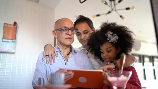 family using digital tablet together at home - foster care stock videos & royalty-free footage