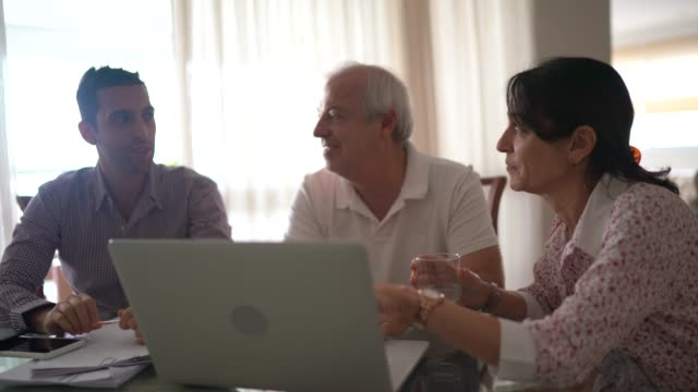 family using laptop at living room - baby boomer stock videos & royalty-free footage