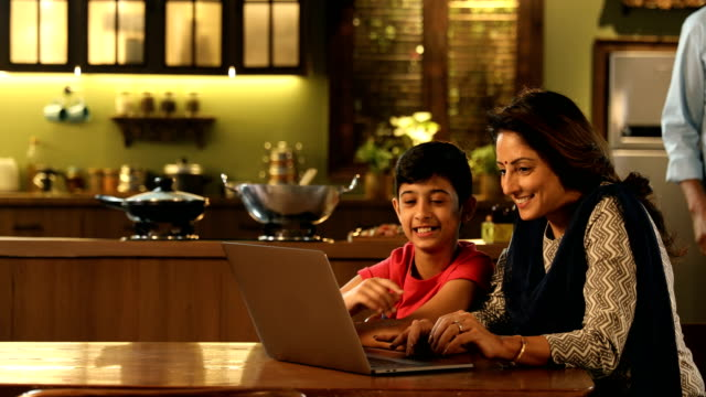 ms family using laptop together at home / delhi, india - 立つ点の映像素材/bロール