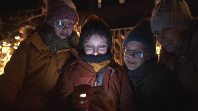 vidéos et rushes de famille utilisant le smartphone sur le banc de stationnement la nuit - photo messaging