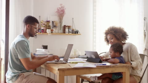 family using technologies at table in kitchen - three people stock videos & royalty-free footage