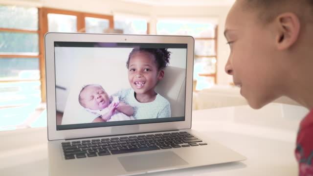 vídeos y material grabado en eventos de stock de family using video chat to meet newborn baby - negro