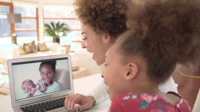 family using video chat to meet newborn baby - voip stock-videos und b-roll-filmmaterial