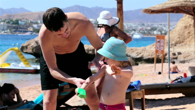 family vacation at sea. caring father smears cream to the skin of the child. - beach umbrella stock videos and b-roll footage