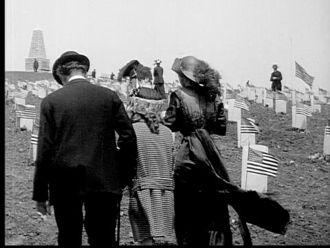 1913 ms b&w family visiting grave in cemetary decorated with american flags - place concerning death stock videos and b-roll footage