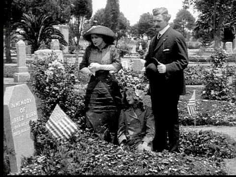 1913 ms b&w family visiting grave in cemetary decorated with american flags - 1913 stock videos & royalty-free footage