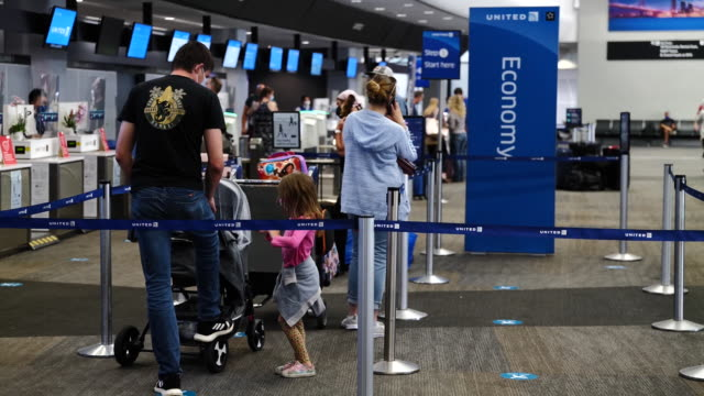 family waiting in line to check-in counter at san francisco international airport in san francisco, california, u.s., on thursday, october 1, 2020. - airport check in counter stock videos & royalty-free footage