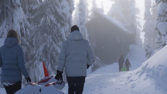 family walk along snowy path towards distant chalet - ascentxmedia stock videos & royalty-free footage