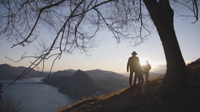 familjevandring längs spår till synvinkel, under träd vid solnedgången - förälder och barn bildbanksvideor och videomaterial från bakom kulisserna