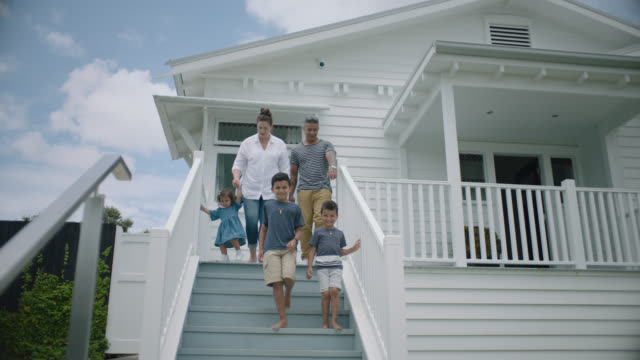 Family walk down the front steps of their new home