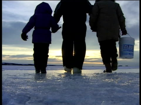 family walk hand in hand over ice sheets with sun in distance bearing straight - inuit bildbanksvideor och videomaterial från bakom kulisserna