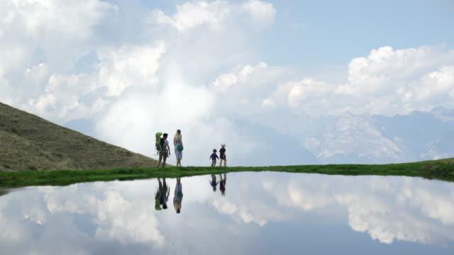 vídeos de stock e filmes b-roll de family walking along alpine lake, view of clouds and mountains in the distance - top peça de roupa