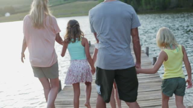 MS of family walking along jetty by lake