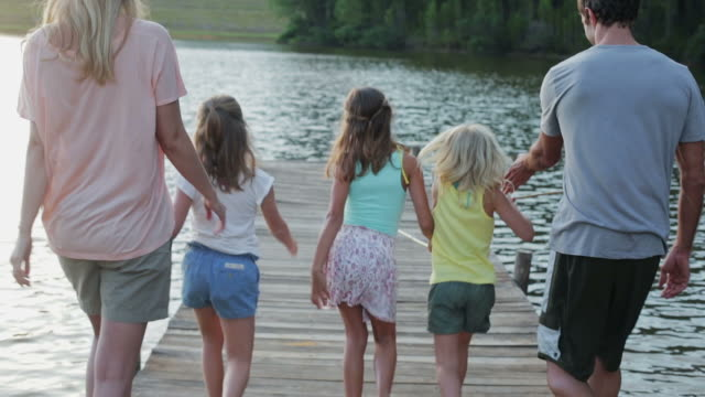 ms of family walking along jetty by lake - family with three children stock videos & royalty-free footage