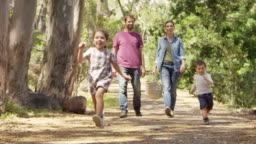 Family Walking Along Path Through Forest Together