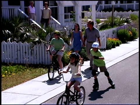 vídeos de stock e filmes b-roll de family walking and riding in sidewalk - família com quatro filhos