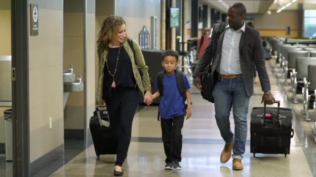 Family walking at an airport with suitcases
