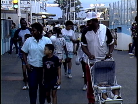 family walking down coney island boardwalk - coney island brooklyn stock videos & royalty-free footage