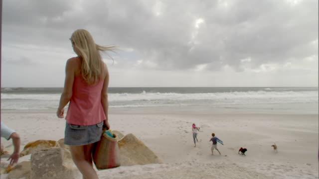 vídeos y material grabado en eventos de stock de sm ws family walking down onto beach for picnic/ cape town, south africa - llegada