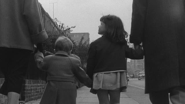 1956 WS Family walking down street holding hands / London, England, United Kingdom