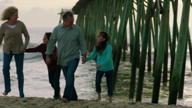 family walking from shore holds hands (slo-mo) - wilmington north carolina stock-videos und b-roll-filmmaterial