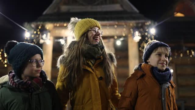 vidéos et rushes de famille marchant dans la petite ville décorée de noël - vêtement chaud