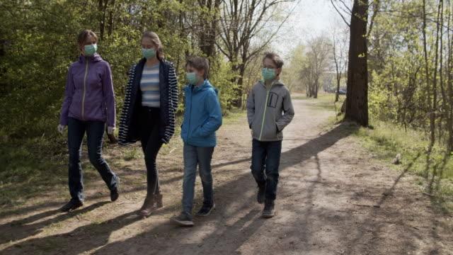 stockvideo's en b-roll-footage met familie die in stadspark tijdens covid-19 pandemie loopt - operatiemasker