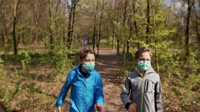 vídeos de stock e filmes b-roll de family walking in forest during covid-19 pandemic - ensolarado