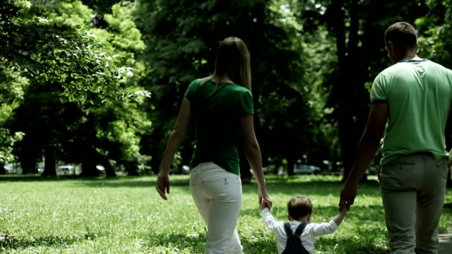 family walking in the park - two parents stock videos & royalty-free footage