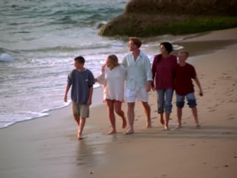 stockvideo's en b-roll-footage met a family walking on a beach - familie met drie kinderen