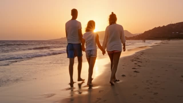 vídeos de stock, filmes e b-roll de família caminhando numa praia ao pôr do sol - solar flare