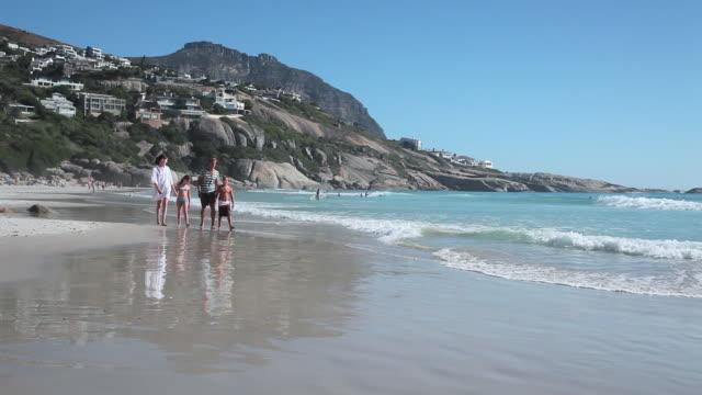 Family walking on beach and children running