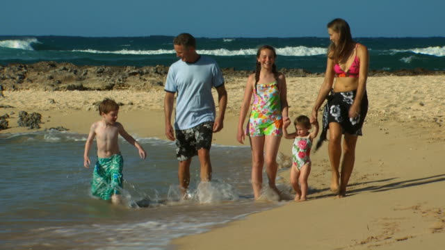 family walking on beach holding hands - 12 23 mesi video stock e b–roll