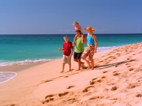 family walking on beach - gemeinsam gehen stock-videos und b-roll-filmmaterial