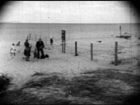 vídeos y material grabado en eventos de stock de family walking on beach w/ suitcases near barbed wire fence, sign 'halt! weitergehen verboten' . angled barbed wire fencing. behind blonde girl... - 1952