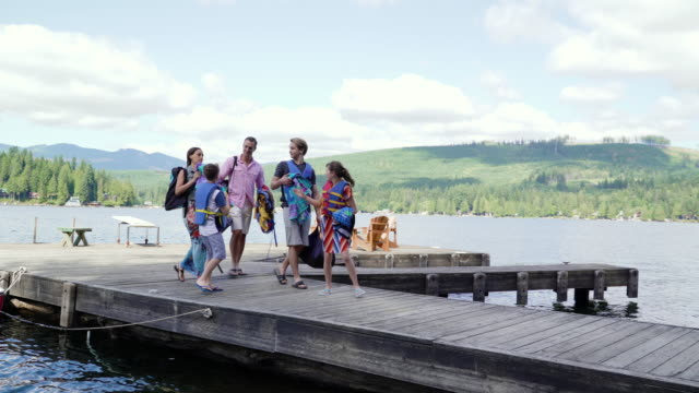 Family walking on jetty by Lake Connaught, Washington, USA.