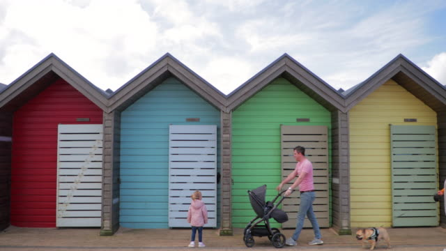 family walking past colourful beach huts - beach house stock videos & royalty-free footage