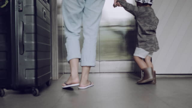 family walking to elevator with suitcase and bang. - human foot stock videos and b-roll footage