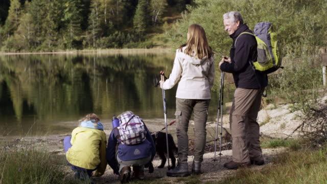 family walking to mountain lake, pan shot, close