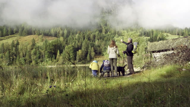 family walking to mountain lake, pan shot, distance shot - familie mit zwei generationen stock-videos und b-roll-filmmaterial
