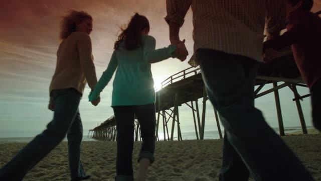 vídeos y material grabado en eventos de stock de family walking to shore holding hands (slo-mo) - wilmington carolina del norte