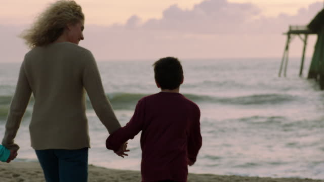 family walking to shore holds hands (slo-mo) - enkelin stock-videos und b-roll-filmmaterial