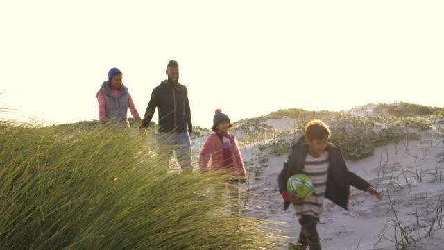 vídeos y material grabado en eventos de stock de family walking together amongst sand dunes on the beach - familia con dos hijos