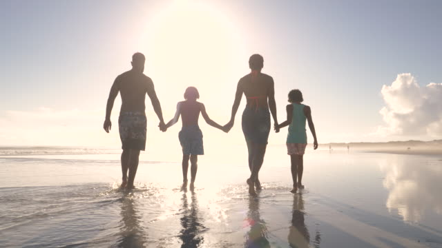 stockvideo's en b-roll-footage met family walking together on an idyllic beach at sunset - op de rug gezien