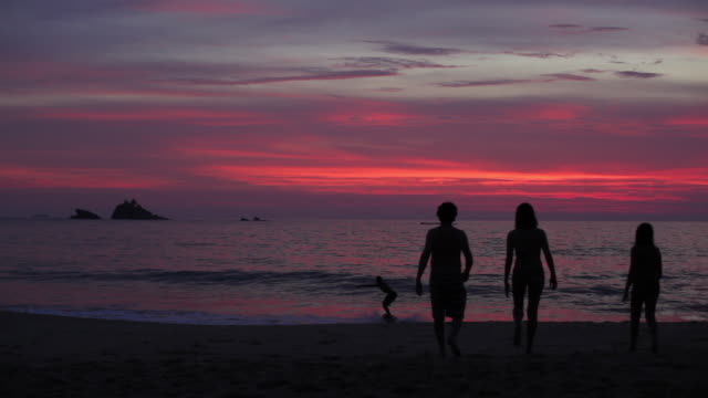 Family walking towards the sea at sunset