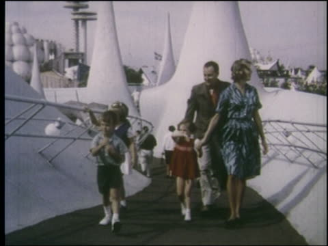 stockvideo's en b-roll-footage met 1964 family walking up ramp toward camera at ny world's fair - 1964