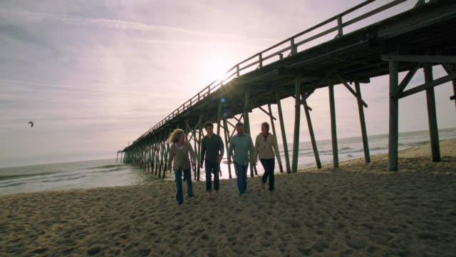 a family walks along a beach. - wilmington north carolina stock-videos und b-roll-filmmaterial