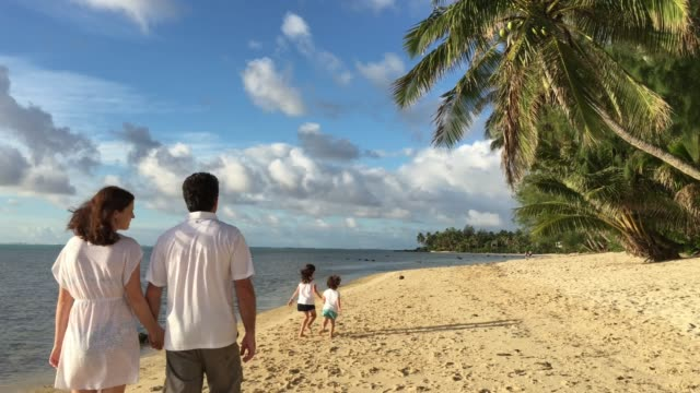 family walks along  a tropical pacific island beach - cook islands stock videos & royalty-free footage