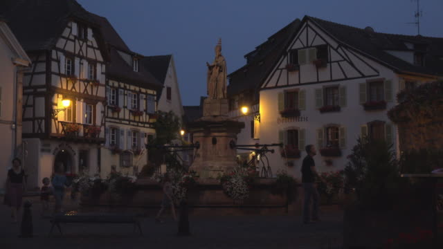A family walks at fountain at Chateau square in a picturesque village at night