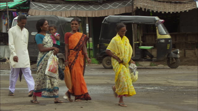 A family walks down an urban street in New Delhi. Available in HD.